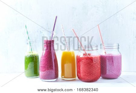 Colorful vegan smoothies with raspbeerries, blueberries, banana, pineapple, mango, arugula, spinach and apple