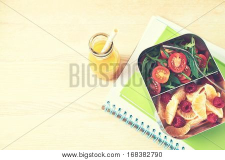 Lunch box with tomato salad and fruits