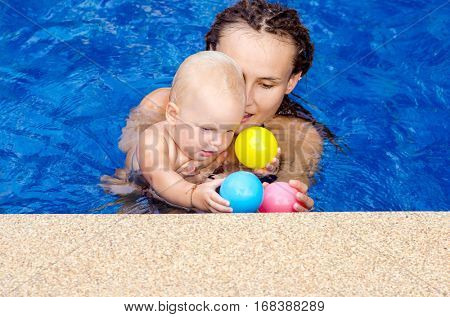 Mom teaches a child to swim. Coach teaches toddler to swim in the pool. They play with a ball.