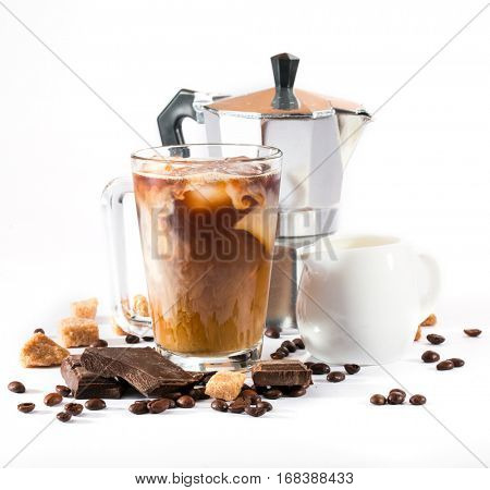 ice coffee in a tall glass with cream and coffee beans, pieces of chocolate and coffee pot on a white background
