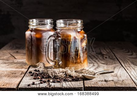 ice coffee in a jar mug with cream and coffee beans on a wooden background