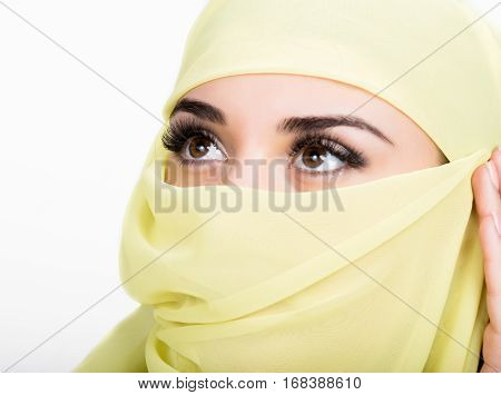 Asian girl with brown eyes posing in a yellow scarf, muslimah model in hijab isolated in white background.