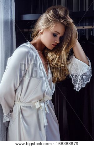Beautiful sexy blonde in underwear and robe is in the wardrobe chooses clothes and posing