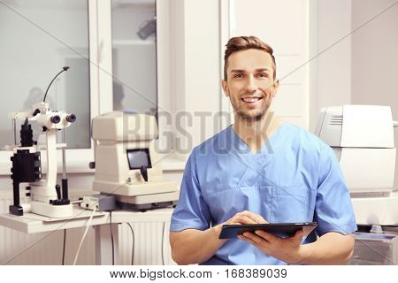 Handsome young ophthalmologist with tablet computer in clinic