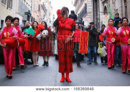 Rome Italy - January 28 2017: Chinese women in traditional dress playing the bongos in the streets of the capital during the procession celebrating the Chinese New Year in the year of the rooster.