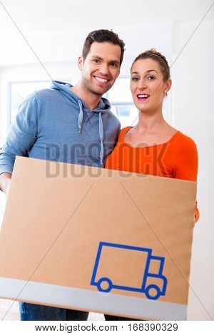 Couple, woman and man, moving house carrying packing cases
