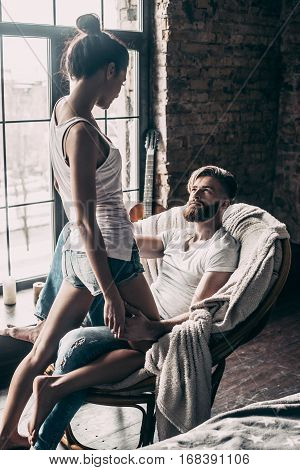 Love and passion. Attractive young woman flirting with her boyfriend while standing in front of him at home