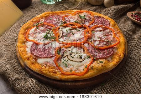Delicious italian pizza served on sackcloth near scattered kitchen utensils and food to prepare