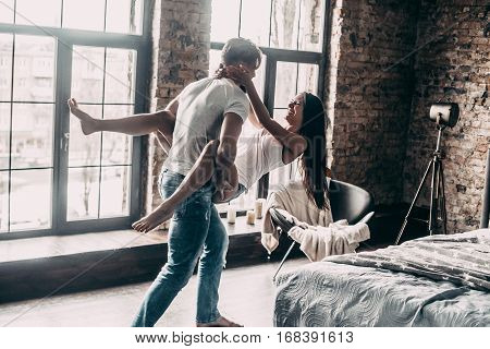 Love forever. Young passionate couple having fun together and looking happy while handsome young man carrying his girlfriend in hands