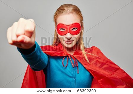 Woman dressed as a superhero with clenched fist for carnival