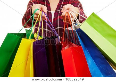 The hands of a woman carry a lot of colorful shopping bags
