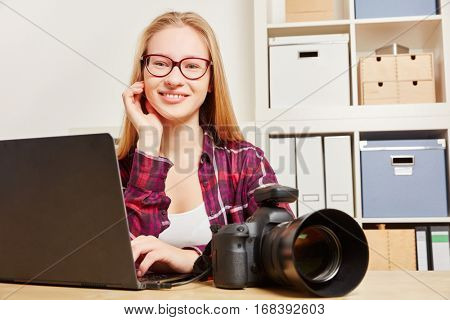Woman as a photographer with laptop and DSLR camera sitting in her office