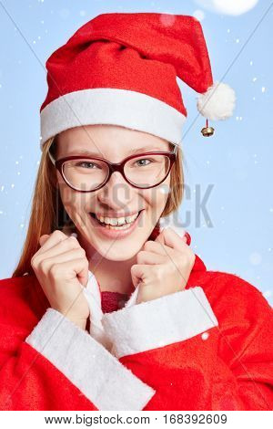 Smiling woman in the snow dressed as Santa Claus with a red cap for christmas