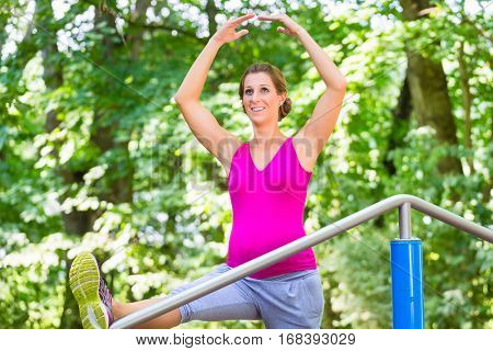 Pregnant woman doing pregnancy yoga on fitness trail