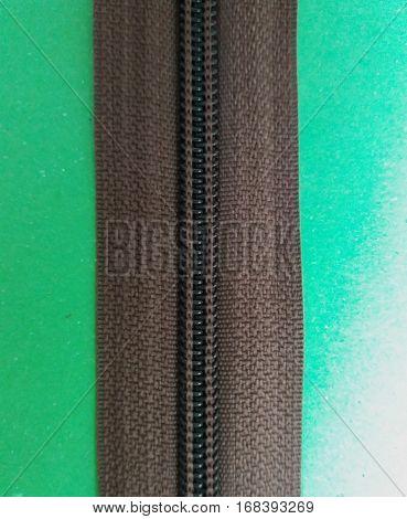 Brown zipper or zip fastener over green background