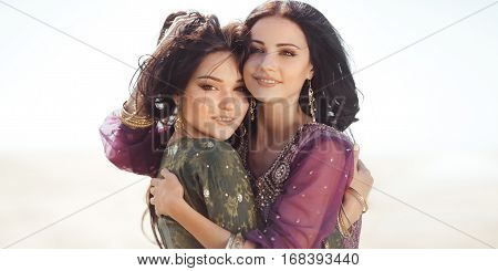 Two friended women sisters against sky white background outdoors. Creative fashion shot of gorgeous models in traditional Indian Arabian dresses and jewelry. Friends Friendship Smiling Together Posing Consept.