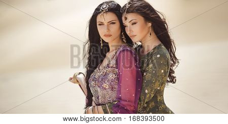 Adventure of two sisters serious princesses standing in the desert and looking at landscape. Two beautiful mixed race asian caucasianl girls enjoy a joint journey. Creative art fashion portrait shot of two gorgeous attractive models with l