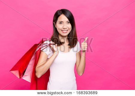 Woman holding shopping bag and finger point up
