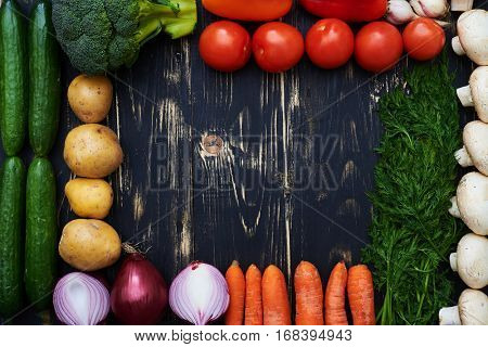 Overhead shot of empty space encircled with seasonal vegetables over wooden flat layout. Vegetables on dark wooden background