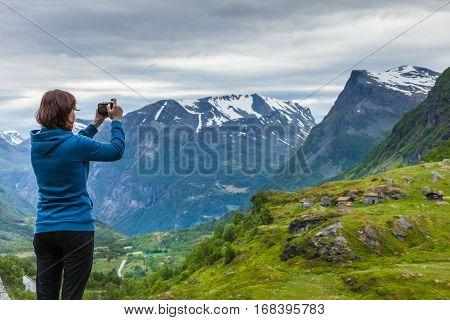 Tourist Taking Photo In Mountains Norway