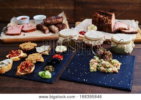 Close-up of big set of different appetizers and main courses served over wooden background. Small appetizers arranged on a cutting board, salads in jars