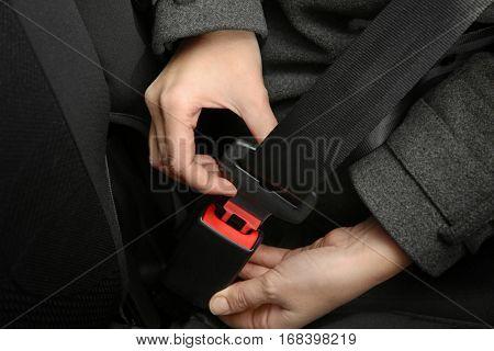 Woman fastening seat belt in car, closeup