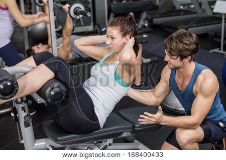 Trainer man helping woman doing crunches abs in gym
