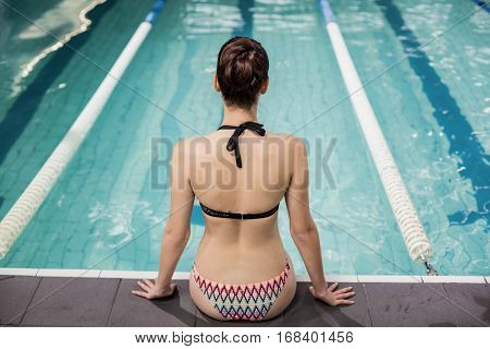 Rear view of a brunette in swimsuit sitting poolside