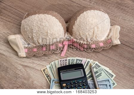 beige bra and calculator with money close up