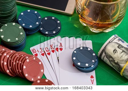 from 10 to Ace heart straight flush on poker and casino chips money on green table