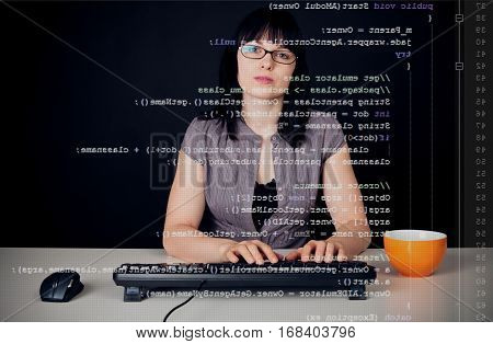 young woman with glasses sitting in front of a computer, programming. the java code she is working on can be seen through the screen.