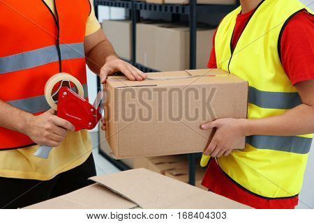 Closeup of workers packing parcels with sticky tape at warehouse