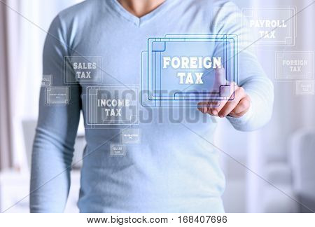 Man pushing FOREIGN TAX button on virtual screen. Taxation concept