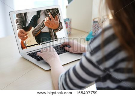 Woman watching record of musical performance online on laptop. Video call and chat concept.