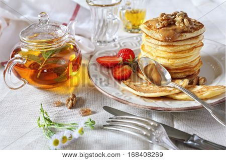 Pancakes with caramel sauce walnuts strawberries and herbal tea