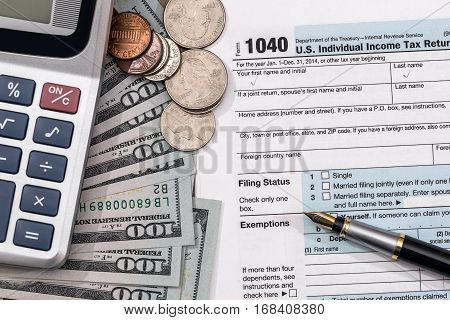 U.S. 1040 tax return form with dollar pen and calculator.