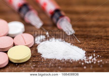 Drug syringe and cooked heroin on desk.