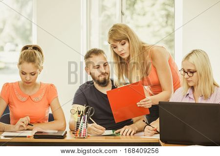 Teaching Concept. Female young teacher or tutor with adult students in classroom with papers laptop computer. Studies course