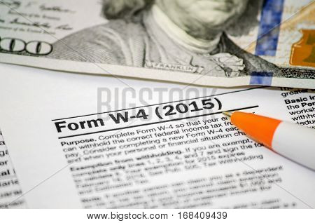 TAX W-4 pen and dollar close up