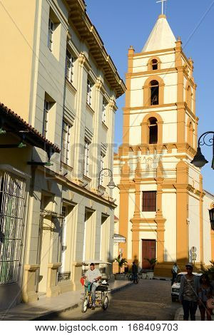 Camaguey Cuba - 11 January 2016: Man driving a bike-taxi in front of Nuestra Senora de la Soledad church in Camaguey Cuba