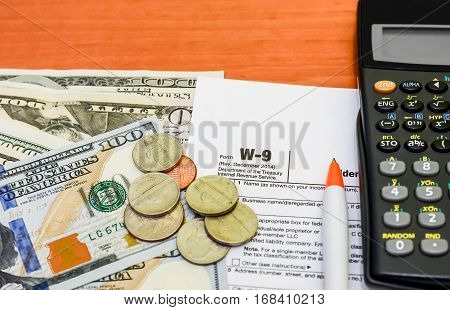Income Taxes. w-9 dolar coin pen close up