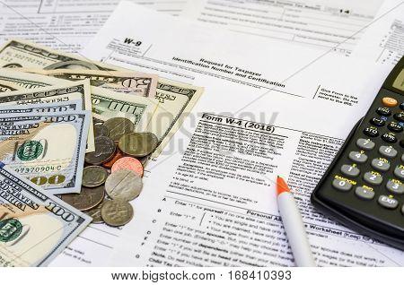 tax form w-4 coin dollar  pen close up