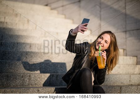 Young woman taking selfie with mobile phone while drinking juice with straw on sunny day