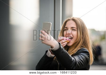 Teen girl taking selfie while eating donut in street