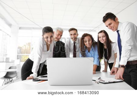 Business training concept. Colleagues looking at laptop screen in office