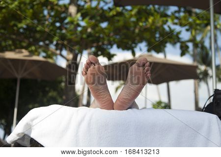 Legs of the sunbathing person show that the person sleeps
