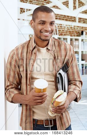 Happy smiling young black man listening to music on earbuds, holding coffee and sandwich.