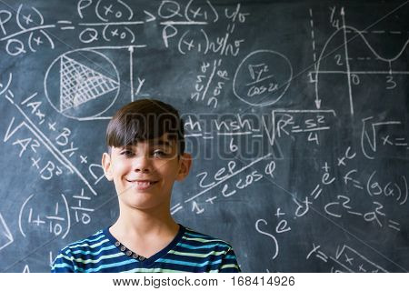 Concept on blackboard at school. Young people student and pupil in classroom. Smart hispanic boy writing math formula on board during lesson. Portrait of male child smiling looking at camera