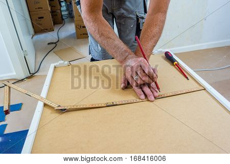 Frederikssund, Denmark, July 19, 2016: Carpenter working with yard stick and pencil. He measures a cabinet to put it on the wall.