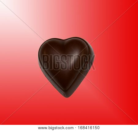 Brown chocolate heart on a red background